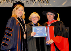 Mentor Cynthia Bates, center, is presented with the Chancellor's Award for Excellence in Teaching by Acting President Meg Benke and Dean Gerald Lorentz at the college's recent Northeast Center graduation ceremony.