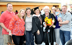 Grandmother and graduate Patricia Rampolla '13, center right with flowers, is joined by David Rampolla, far right, Allison and Amy Rampolla, commencement speaker Carol Evans '77, Jen and Mark Rampolla, who is holding grandson John.