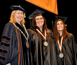 Acting President Meg Benke congratulates Jennifer Jorgensen and her sister Katelyn, one of the student speakers.