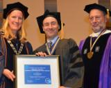 Professor Ian Reifowitz stands between President Merodie A. Hancock and Dean Michael A. Spitzer at the college's 2014 Long Island commencement exercise. Reifowitz was presented with a medallion and framed certificate in recognition of being named a 2014 recipient of the SUNY Chancellor's Award for Excellence in Scholarship and Creative Activities.