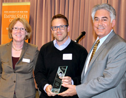 Chris Fowler, center, founder and executive director of SyracuseFirst, is presented with the college's 2014 Excellence in Environmental Sustainability Award by Nikki Shripmton, dean of the college's Central New York Center, and the 2011 award recipient Al Stirpe, (D-Cicero) who represents the people of assembly district 127.