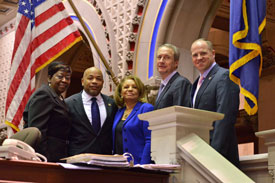 Elected officials join associate professor Catherine Collins, at center, after her unanimous election to the Board of Regents during the annual joint session of the state Legislature. Assemblywoman Crystal Peoples-Stokes stands at far left with state Assembly Speaker Carl E. Heastie, Collins, Assemblyman Sean Ryan and state Sen. Timothy M. Kennedy on the assembly chamber dais. Photo/NY Assembly
